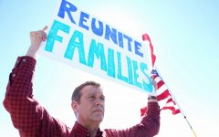 People held up signs behind the media  during the press conference at the Tornillo- Guadalupe Port of Entry.