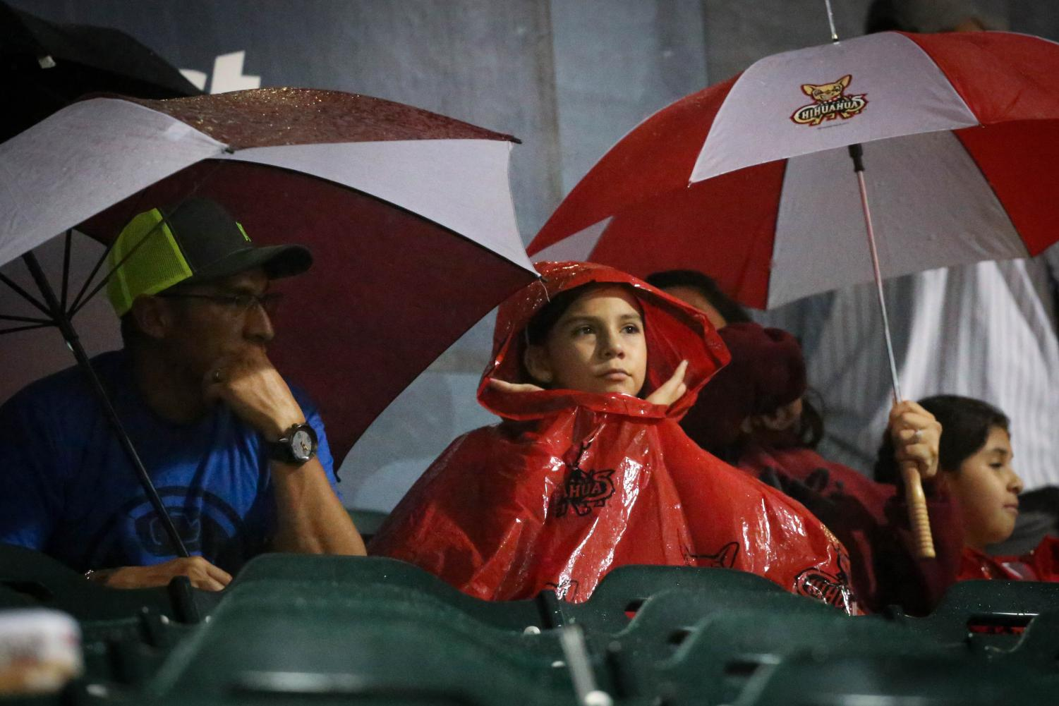 The+crowd+take+out+their+umbrellas+as+the+rain+comes+back+during+the+fourth+inning+at+the+delayed+game.+