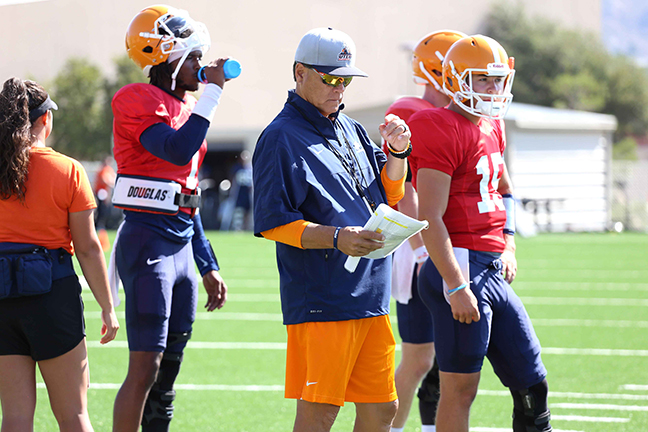Offensive coordinator Mike Canales goes over the playbook with Kai Locklsey (left) and Calvin Brownholtz (right) camp.