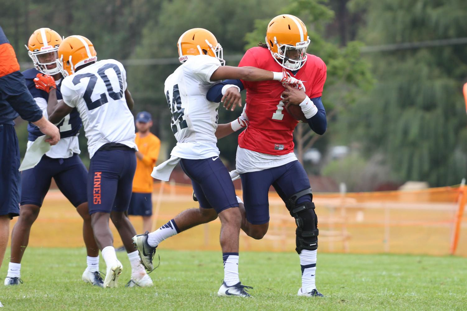 Quarterback+Kai+Locksley+protects+the+ball+as+he+runs+past+the+defender+during+practice+at+Camp+Ruidoso.+