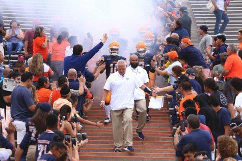 Football head coach Dana Dimel leads his team down the Mine Shaft during pre-game.
