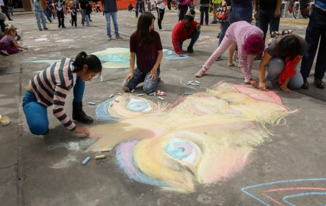 Artist work together to finish a chalk piece at day two of Chalk the Block on Saturday, Oct. 13.