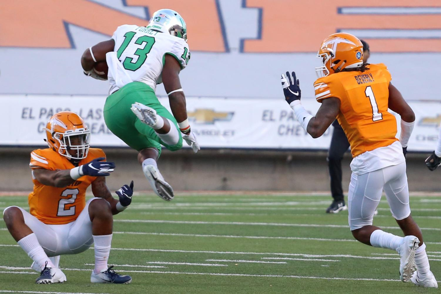 UNT+sophomore+running+back+Deandre+Torrey+goes+through+both+UTEP+senior+defensive+back+Kalon+Beverly+and+junior+defensive+back+Michael+Lewis.+