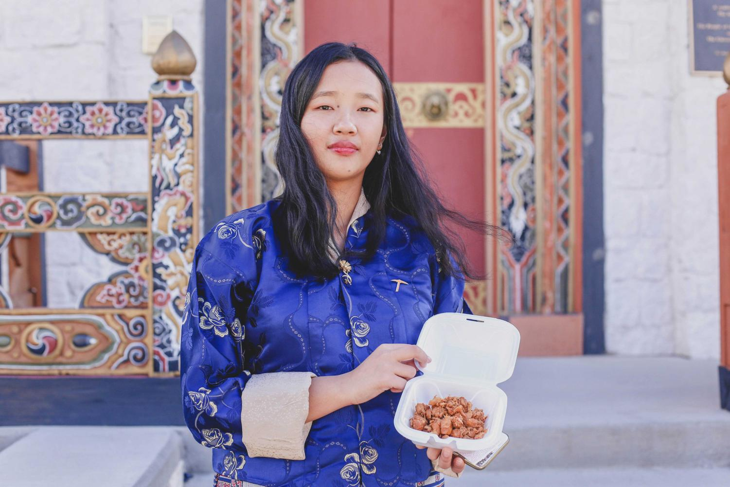 Freshman environmental science major Yeshey Seldon poses in front of the Bhutan Temple holding Jasha Maru (Spicy Chicken Curry) sold by the Bhutanese Student Association at the International Food Fair on Monday, Nov. 12.