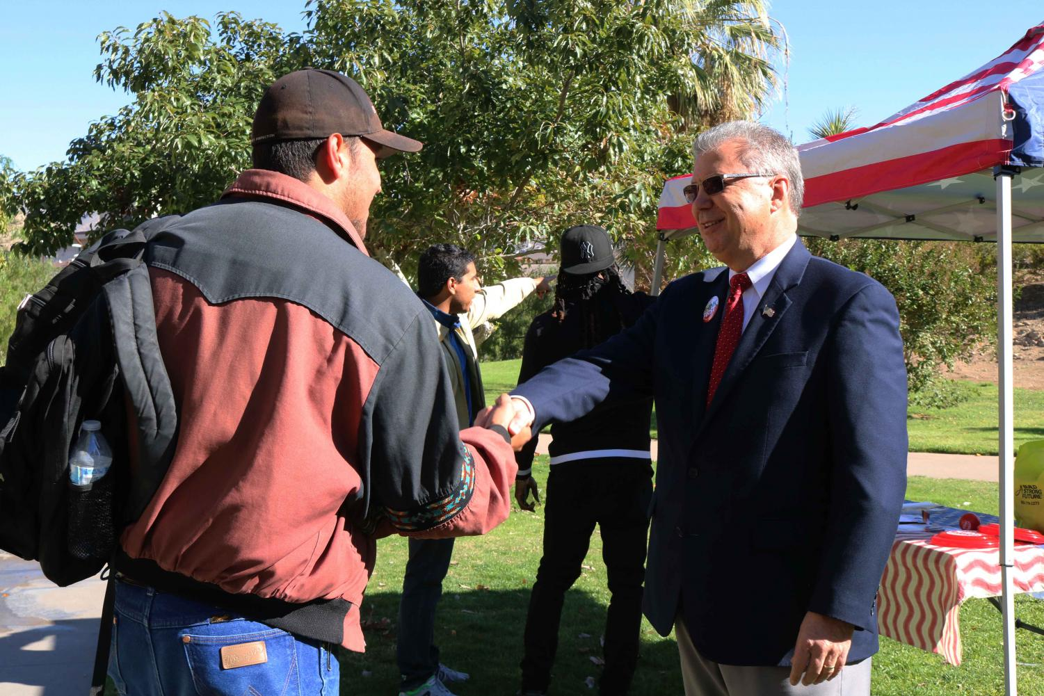 Candidate Rick Seeberger shakes hands with formal student.