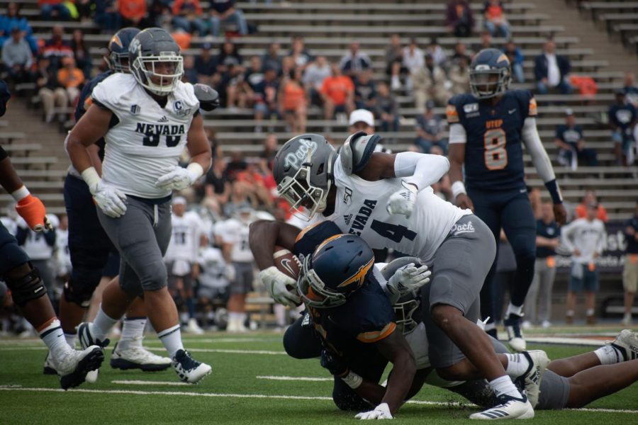 UTEP+player+Joshua+Fields+is+finally+brought+down+by+two+defenders+against+the+University+of+Nevada.