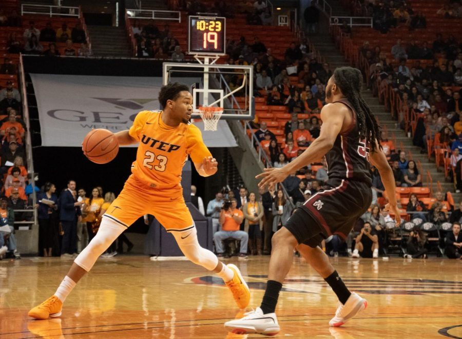 Sophomore guard Nigel Hawkins evades around the defender while playing against NMSU at the Don Haskins Center on Dec.3