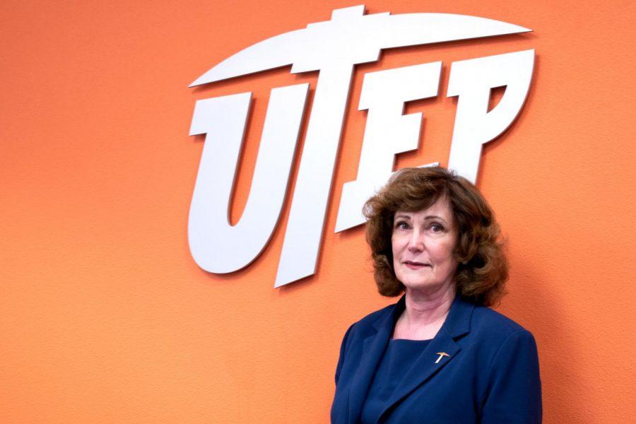 Leslie Robbins , UTEP's new Dean of Nursing, stands beneath the seal of UTEP.
