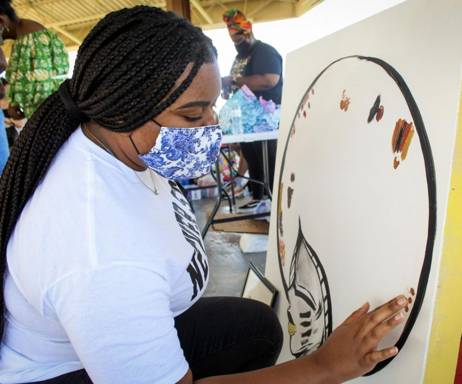 Participant of Juneteenth march at Veterans Park adds her personal touch to a community picture promoting unity June 19, 2020.