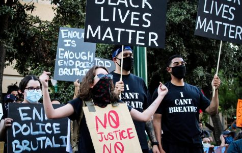 Protestors hold signs demanding justice for George Floyd and the end of police brutality at Aztec Calendar Park, June 2.