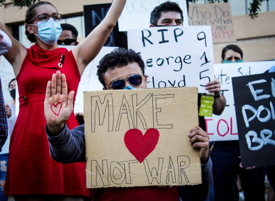 Protester holds up sign with message of make love not war at downtown rally June 2.