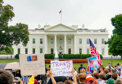 Protestors hold signs outside the White House, against former President Donald Trump