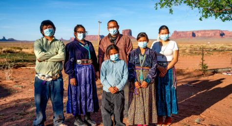 A Navajo family stands outside its home with face masks to prevent COVID-19 at Monument Valley, Arizona.